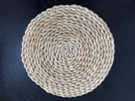 Circular natural brown dry grass rattan fibers craft on dark wall background