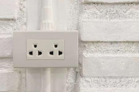 double socket plug with white brick wall background