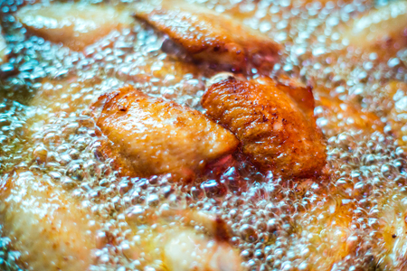 Close up fried chicken wings in boiling oil, in a cast iron frying.