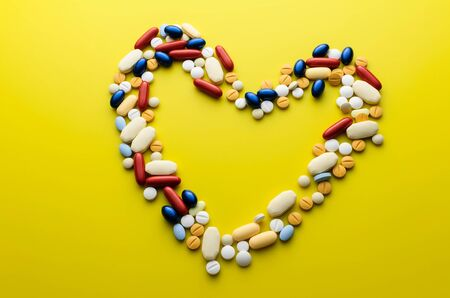 medicate: Colorful pills and tablets in shape of heart