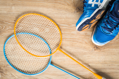 badminton: Badminton accessories, shoes and a rocket on a wooden floor