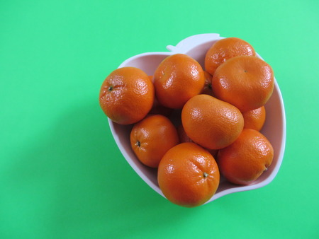 clementines: Bowl of clementines on green background