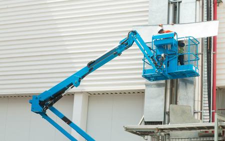 Hydraulische mobiele constructie platform verheven naar een blauwe Stockfoto