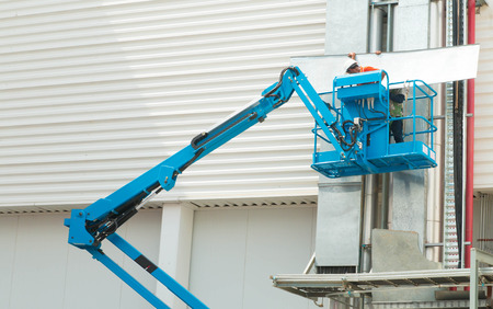 Hydraulic mobile construction platform elevated towards a blue Standard-Bild