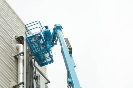 construction platform: Hydraulic mobile construction platform elevated towards a blue Stock Photo
