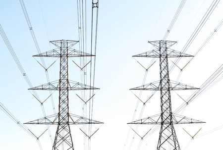 energy needs: a highvoltage electricity pylons against blue sky and sun rays