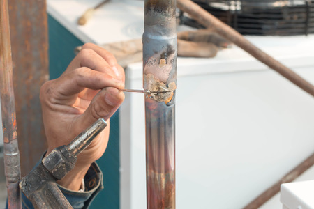 custom home: Plumbing contractor works sweating the joints on the copper pipe domestic water system on a luxury custom home Stock Photo