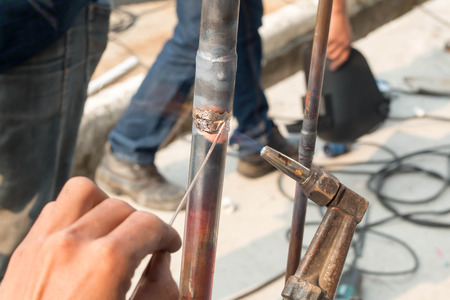 Plumbing contractor works sweating the joints on the copper pipe domestic water system on a luxury custom home Foto de archivo