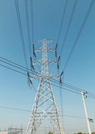 torres el�ctricas: unas torres el�ctricas de alta tensi�n contra el cielo azul y los rayos del sol
