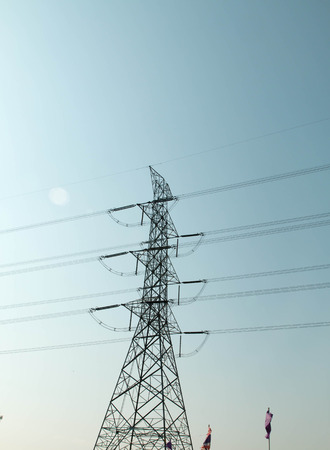 energy needs: a high-voltage electricity pylons against blue sky and sun rays