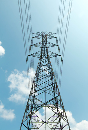 energy needs: a power mast of a high voltage transmission line against blue sky with sun