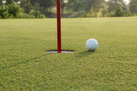golf ball: golf ball on lip of cup Stock Photo