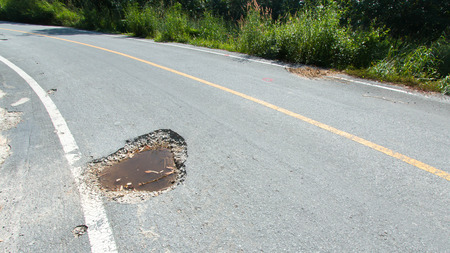 local government: Restricted local government budgets are reflected in potholes and damaged roads Stock Photo