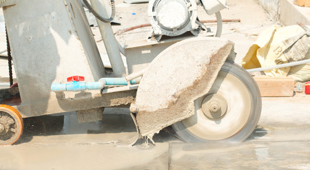 asphalt paving: Construction worker cutting Asphalt paving stabs for sidewalk using a cut-off saw. Profile on the blade of an asphalt or concrete cutter with workers shoes and protective gear.