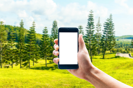 hand position: Hand using smartphone mobile in the vertical position, background blur of Beautiful landscapes