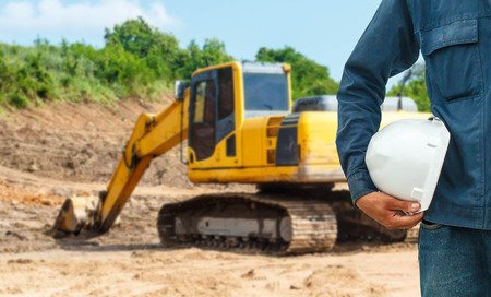 The engineering and safety helmets stood on the details of Closeup skid steer loader excavator at road construction work Stock Photo