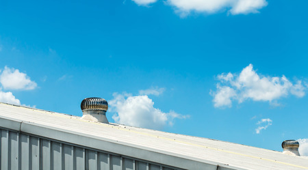 Air ventilator on the roof of factory.Natural Roof Ventilators on the roof top spinning and take cool wind into the building. Standard-Bild