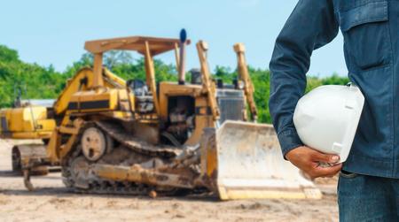 De techniek en veiligheidshelmen bevonden zich op de details van de close-up schrankladerladergraafwerktuig bij de wegenbouw