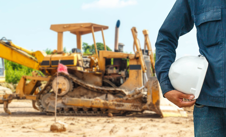 skid steer loader: The engineering and safety helmets stood on the details of Closeup skid steer loader excavator at road construction work Stock Photo