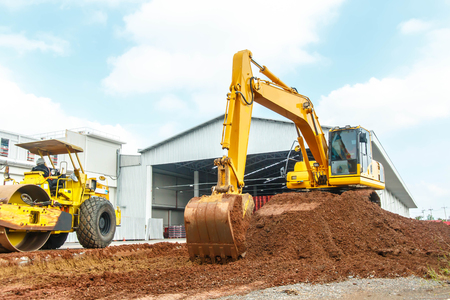 earthmover: Excavator and grader working at construction site Stock Photo