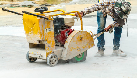 Construction worker cutting Asphalt paving stabs for sidewalk using a cut-off saw. Profile on the blade of an asphalt or concrete cutter with workers Banco de Imagens