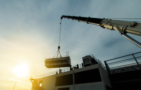 mobile crane lifting Cooling machine, silhouettes at sunset Banco de Imagens