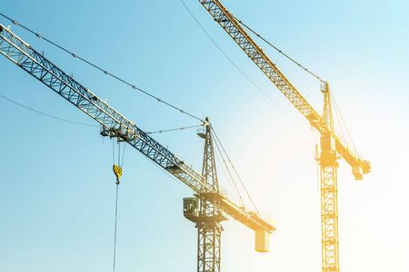 Construction crane tower on blue sky background. Crane and building working progress Construction concept. Site. New buildings