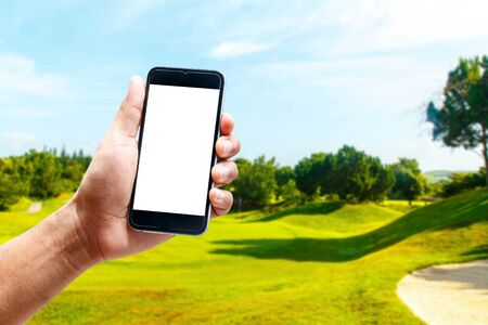 Hand using smartphone mobile in the vertical position, background blur of golf.
