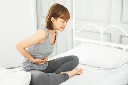 young beautiful asian woman wearing gray clothes,Wake up in a white bed in the morning, The body aches, Hug hands on the stomach Curled up with abdominal pain, stomachache,pain,painful