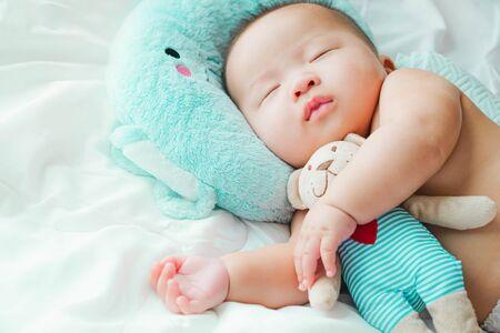 Porträt eines neugeborenen asiatischen Babys auf dem Bett, Ein Kind, das auf einem schlafenden Bett ruht