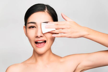 young beautiful asian woman with clean and bright skin, Cosmetic Beauty Concept, hands touch on the cheek, smiling and friendly face isolated on grey background Stock Photo