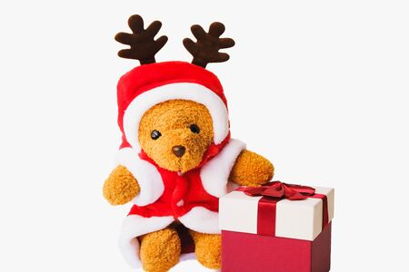 Selective focus,A teddy bear wearing a santa hat With many colorful gift boxes isolated on white background,Christmas day and New Year's gifts