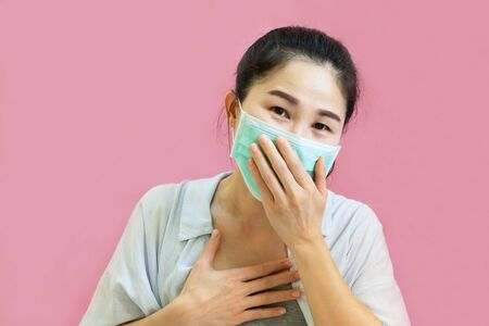 Young asian woman worea gray tank top, Blue shirt and protective masks against virus and air pollution,make gesture Coughing, isolated on pink background