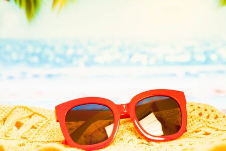 Beach,Funny pineapple in a red sunglasses and hat on the sand against sea and sky.Tropical summer vacation concept. Sunny day on the beach,Selective focus yellow and blue sea