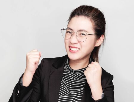Young smart beautiful asian business woman wore black suit and glasses,smart and thinking holding Document, talking phone