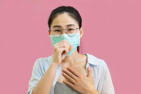 Young asian woman wore a gray undershirt, Blue shirt and protective masks against virus and air pollution,make gesture handful clasped and raised, isolated on pink background,health care concept Stock Photo