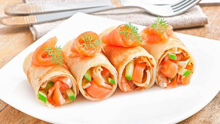 """""""Sushi roll""""Thin dough, fish and vegetables With sour and sweet sauce Served on a white plate Foto de archivo"""