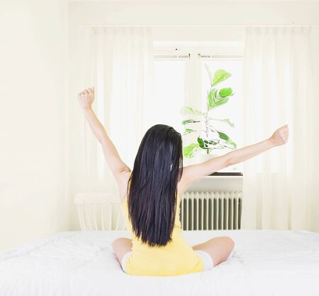 Back of young asian woman wearing yellow undershirt exercising yoga while sitting on a white bed by the window with a thin curtain,
