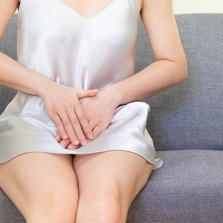 woman wearing white Sleepwear sitting on sofa . Female holding hand to spot of vagina-ache. Concept photo Penis pain.Health care concept,Soft focus