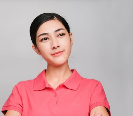 young beautiful asian woman wore pink t shirt, Showed thinking expression , on gray background