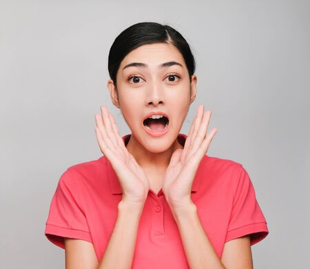 young beautiful asian woman wore pink t shirt, Showed surprised  expression , on gray background Reklamní fotografie