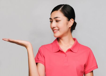 young beautiful asian woman wore pink t shirt, Showed empty hand for product, smart expression , on gray background