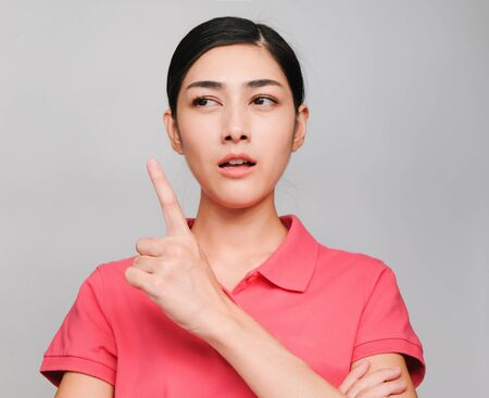 young beautiful asian woman wore pink t shirt, Showed Pointing and thinking expression , on gray background
