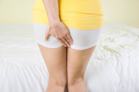 woman holding hand to spot of pain area, sore on her bottom ,She has Butt pain,Hemorrhoids recurrent,health care concept