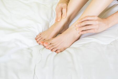 woman suffering from Ankle or leg pain while sitting on bed at home,health care concept Stock Photo