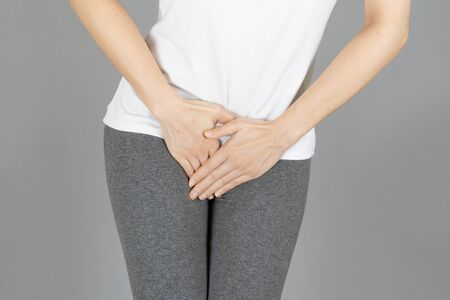 crop image of hand on the crotch area,Penis pain.Health-care,urinary,infection, incontinence,bladder,dysmenorrhea concept on gray background