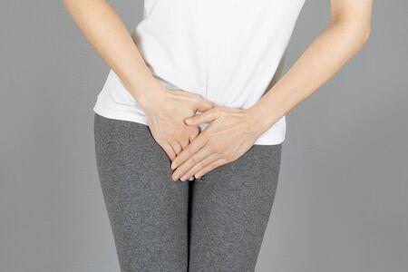 Bild der Hand im Schrittbereich zuschneiden, Penisschmerzen. Gesundheitsversorgung, Harnwegsinfekt, Infektion, Inkontinenz, Blase, Dysmenorrhoe-Konzept auf grauem Hintergrund