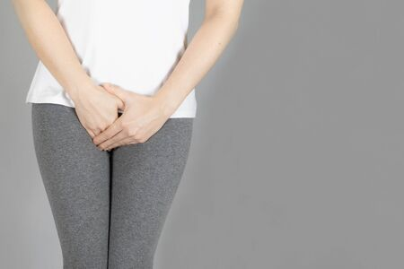 Cropped of woman in gray shorts put her hand on the genitalia area, Penis pain or Itching urinary Health-care concept on gray background