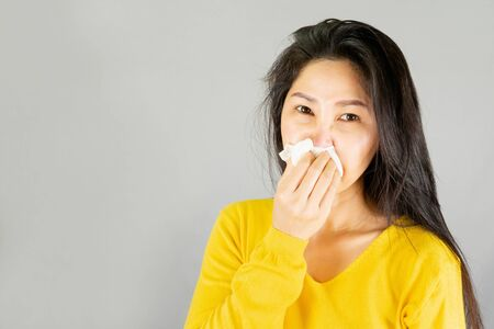 Young Asian woman wearing yellow shirt,Have a cold, wipe the snot isolated on gray background,health care concept with copy space