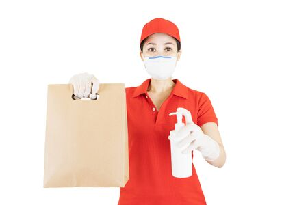 Asian Delivery woman in red uniform isolated on white background.Courier in protective mask and medical gloves delivers takeaway food and spray alcohol cleaning before deliver service under quarantine